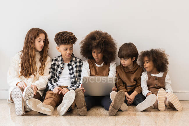 Cute content multiracial kids browsing modern netbook while sitting together in row on floor in light living room — Stock Photo