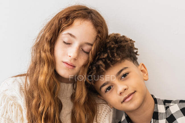 Relaxed multiethnic kids in casual wear sleeping on each others shoulder against white wall in light living room — Stock Photo