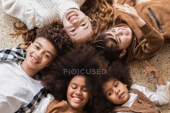 Вид сверху восхищал разнообразных детей в стильной одежде, лежащих на полу вместе по кругу и счастливо улыбающихся — стоковое фото