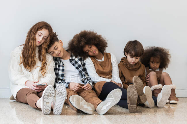 Group of adorable funny multiracial children in stylish wear resting on floor in order of height — Stock Photo