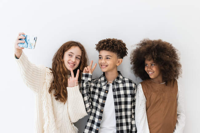 Cheerful positive multiracial children in trendy clothes showing v signs and taking selfie on contemporary mobile phone against white room — Stock Photo