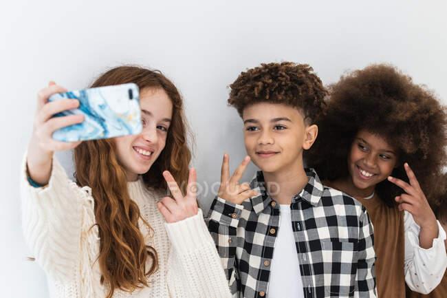 Веселые позитивные многорасовые дети в модной одежде с V знаками и селфи на современном мобильном телефоне против белой комнаты — стоковое фото