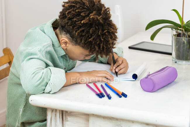 Side view crop diligent African American schoolboy in casual shirt sitting at table and taking notes in copybook while working on home assignment — Stock Photo