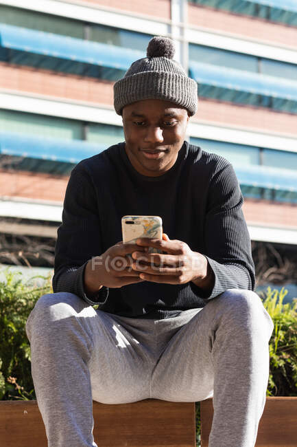 From below of African American male wearing hat and casual clothes browsing mobile phone in sunny park — Stock Photo