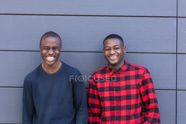 Happy amici afroamericani in abbigliamento casual contro muro grigio guardando la fotocamera — Foto stock