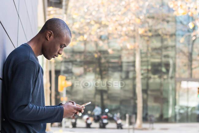 Vue latérale d'attentif Afro-Américain mâle défilant téléphone mobile moderne tout en se tenant contre le bâtiment gris — Photo de stock