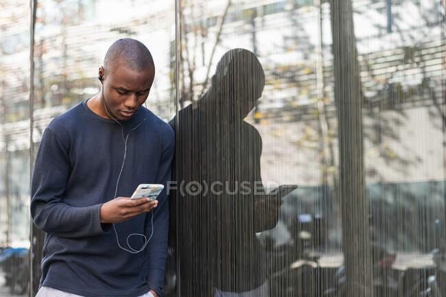 Сторона зору уважного афро - американського чоловіка, який прокручує сучасний мобільний телефон навушниками, стоячи навпроти сірого будинку. — стокове фото