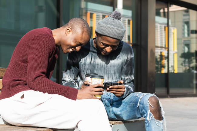 Young content best African American friends with coffee to go and earphones watching cellphone in city — Stock Photo