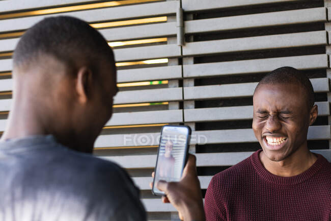 African American male taking photo on smartphone of friend laughing happily with closed eyes — Stock Photo