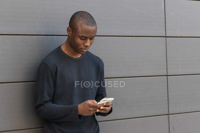 Attentive African American male scrolling modern mobile phone while standing against gray building — Stock Photo