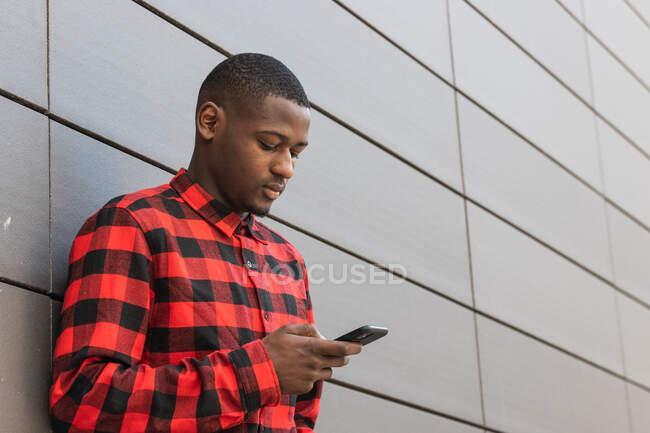 Внимательный афроамериканец, прокручивающий современный мобильный телефон в клетчатой рубашке, стоя напротив серого здания — стоковое фото