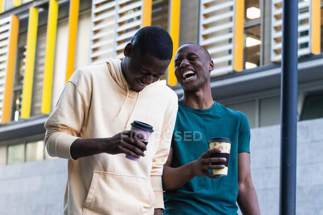 Jeunes partenaires masculins ethniques positifs dans des vêtements décontractés interagissant avec des boissons chaudes pour aller près du bâtiment urbain — Photo de stock