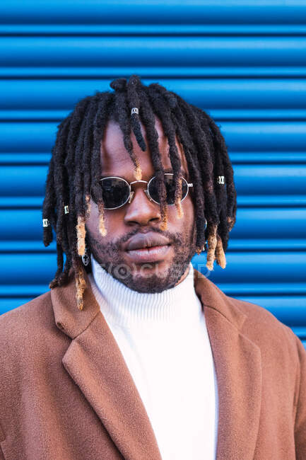 Cool African American male in stylish sunglasses and with dreadlocks standing against blue wall in city — Stock Photo