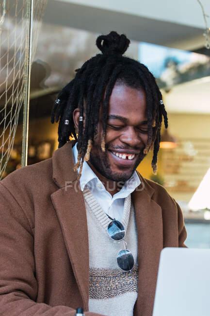 Бічний вид веселого гіпстера чорний чоловік з Афро в дреди сидять за столом з ноутбуком під час роботи над віддаленим проектом в ресторані на відкритому повітрі — стокове фото