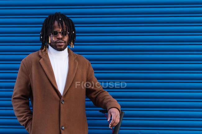 Впевнений дорослий афро-американський гіпстер з африканськими плечима в стильному пальто і сонцезахисні окуляри стоять біля електричного скутера проти синьої смугастої стіни. — стокове фото
