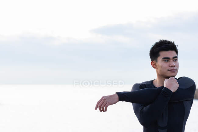 Young Asian male in sportswear stretching arms and shoulders while standing against blurred sea and sunset sky during outdoor fitness workout — Stock Photo