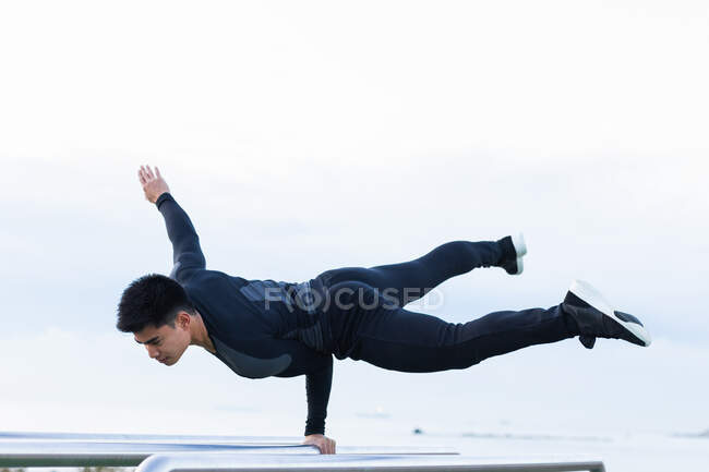 Full body of confident young Asian male gymnast performing handstand on one hand on metal bar while exercising on sports ground — Stock Photo