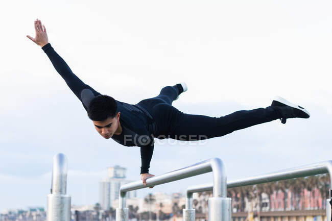 Low angle full body of confident young Asian male gymnast performing handstand on one hand on metal bar while exercising on sports ground — Stock Photo