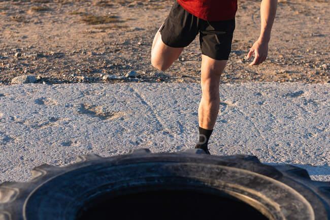 Crop macho anônimo em sportswear fazendo exercício de alongamento para pernas enquanto se aquece perto de pneu no chão de esportes durante o treino ao ar livre — Fotografia de Stock