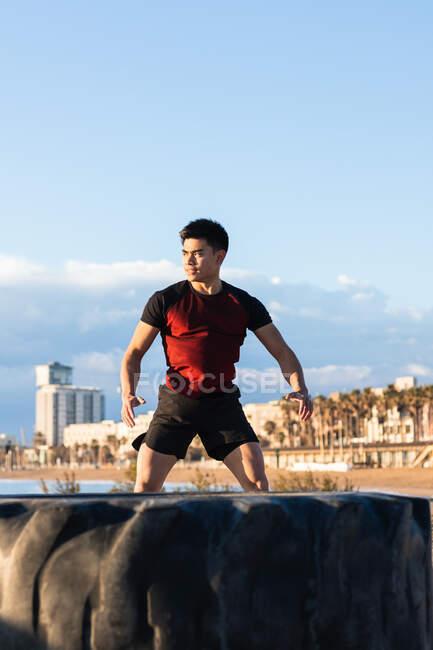 Confiante jovem atlético asiático masculino realizando exercício de salto energético enquanto se prepara para o treino com pneu de carro em aterro urbano — Fotografia de Stock