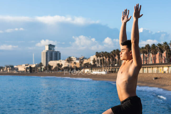 Вид сбоку молодой азиатский мужчина без рубашки, стоящий в позе воина с поднятыми руками во время занятий йогой на пляже — стоковое фото