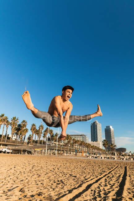 Полное тело мощного молодого азиатского спортсмена с обнаженным туловищем, выполняющего упражнения с широкими ногами, крича над песчаным пляжем во время интенсивной тренировки — стоковое фото
