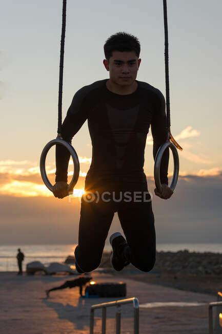 Визначення молодого азіатського спортсмена робить вправи на гімнастичних кільцях під час тренувань на відкритому повітрі проти хмарного сонячного неба. — стокове фото