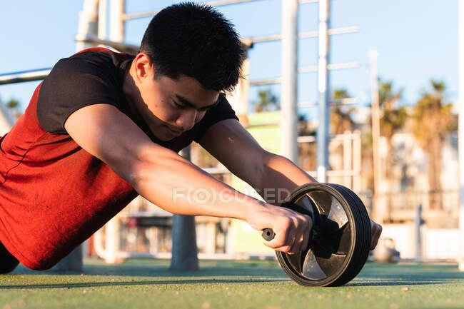 Вид сбоку на неузнаваемый сильный спортсмен мужского пола, тренирующий мышцы живота с бэш-диском во время интенсивной тренировки на спортивной площадке — стоковое фото