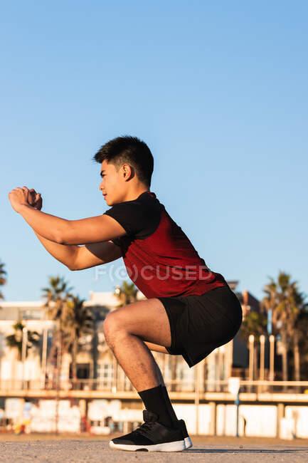 Полный вид сбоку от тела определяется молодой азиатский мужчина в спортивной форме выступающих отрядов во время разминки и подготовки на спортивной площадке — стоковое фото