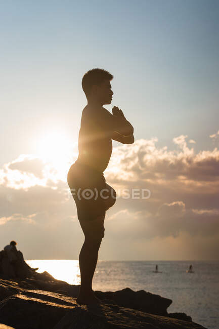 Side view silhouette of unrecognizable male balancing on Tree pose with arms up while practicing yoga against cloudy sundown sky — Stock Photo