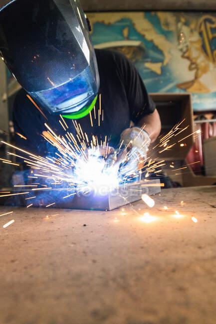 Unrecognizable male master in protective helmet welding metal piece at workbench in workshop — Stock Photo