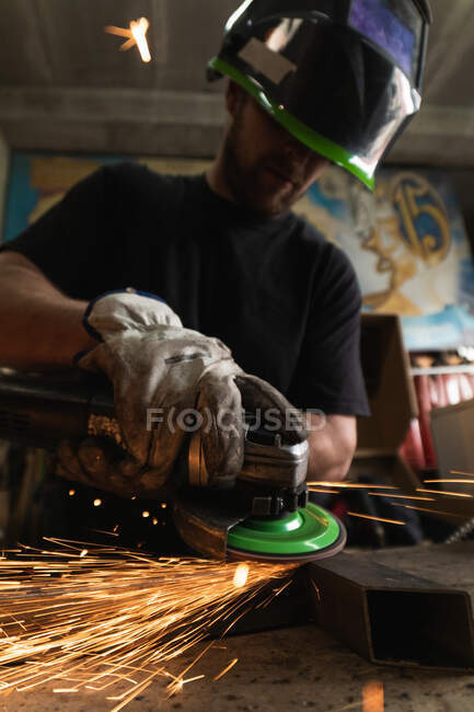 From below unrecognizable male welder in protective hardhat using electric grinder and cutting metal detail in grungy workshop — Stock Photo