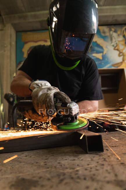 Soldador macho irreconhecível em hardhat de proteção usando moedor elétrico e corte de detalhes de metal em oficina grungy — Fotografia de Stock