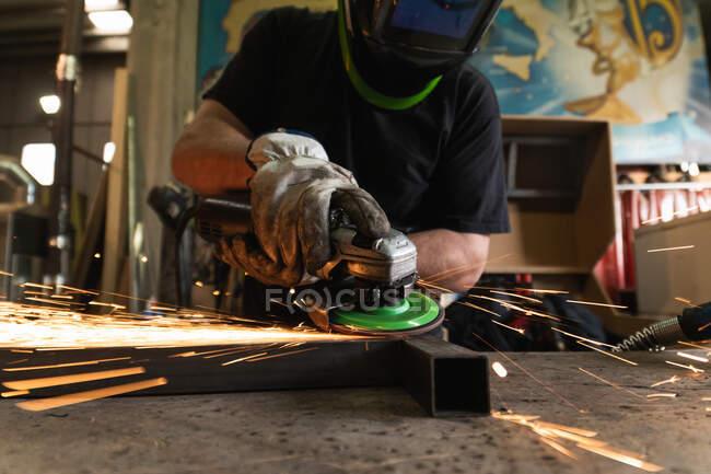 Unbekannter schweißt Schweißer in Schutzhelm mit Elektroschleifer und schneidet Metalldetail in grunziger Werkstatt — Stockfoto