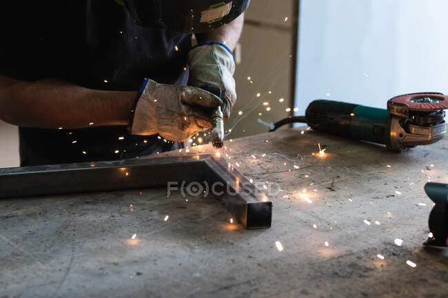 З - під землі нерозпізнаний зварник у захисних рукавицях, що зварюють металеві деталі на затіненій роботі в майстерні. — стокове фото