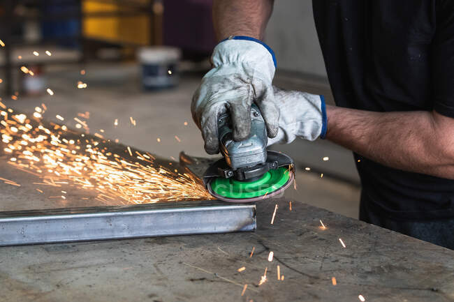Cropped unrecognizable male welder in protective hardhat using electric grinder and cutting metal detail in grungy workshop — Stock Photo