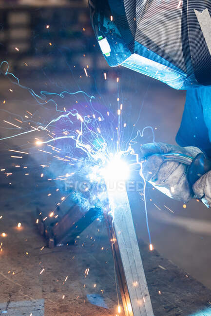 Unrecognizable cropped male master in protective helmet welding metal piece at workbench in workshop — Stock Photo