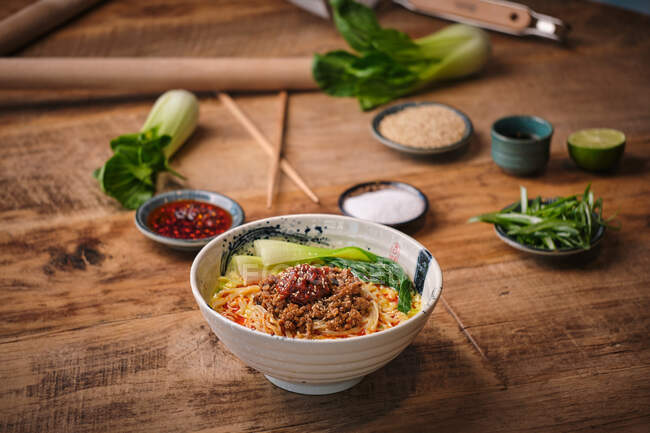 Stock photo of yummy noodles soup with minced meat isolated in wooden background next to sesame seeds and other ingredients. — Stock Photo