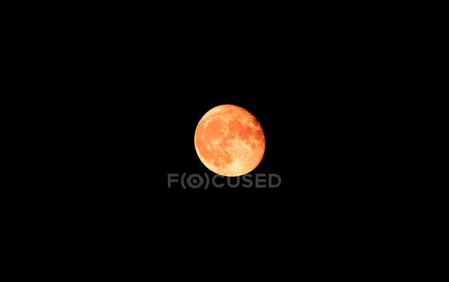 From below scenic view of colorful sphere shaped moon with spots on black background at dusk — Stock Photo