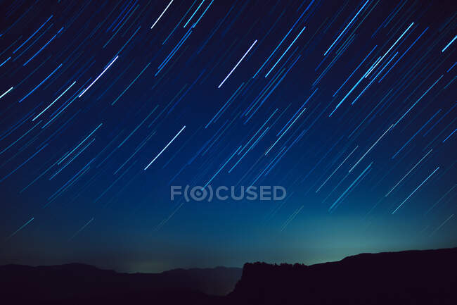 Scenery view of sky with storm of fast meteors over mount silhouette at dusk — Stock Photo