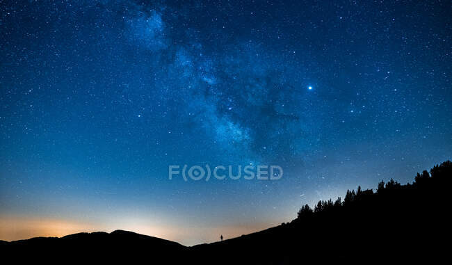 Picturesque view of starry blue sky with clouds over mount with unrecognizable person silhouettes at sunset — Stock Photo