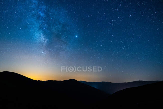 Picturesque view of starry blue sky with clouds over mount with mountains silhouettes at sunset — Stock Photo