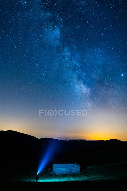 Anonymous traveler silhouette with blue light standing near mountain under colorful sky with stars at night — Stock Photo