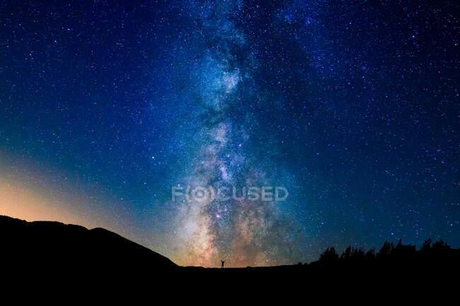 Pintoresca vista del cielo azul estrellado con nubes sobre el monte con siluetas de persona irreconocibles al atardecer - foto de stock