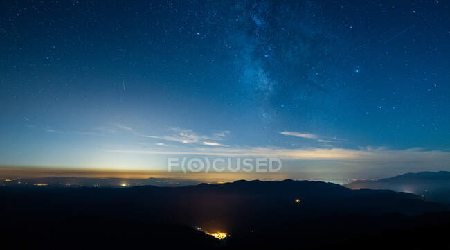 Picturesque view of majestic mount silhouettes under colorful starry sky with clouds at dusk in Spain — Stock Photo