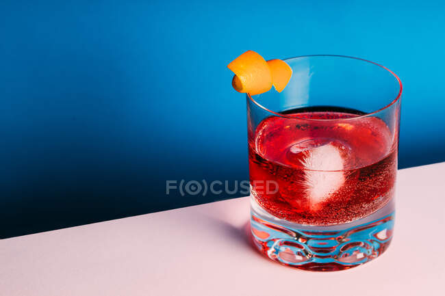 Glass of bitter alcoholic Negroni cocktail served with ice and orange peel on light surface — Stock Photo