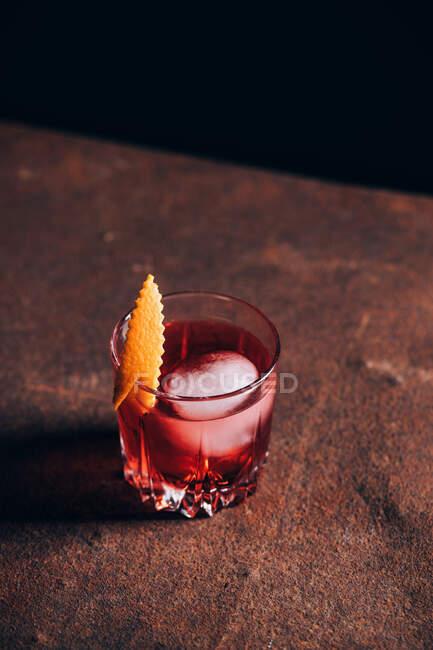 Copa de refrescante cóctel alcohólico Negroni decorado y cáscara de naranja y colocado en la mesa en medio de herramientas barman - foto de stock