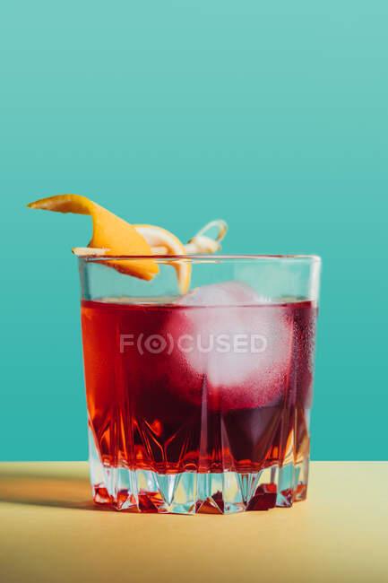 Vaso de cóctel Negroni alcohólico amargo servido con hielo y cáscara de naranja en superficie clara - foto de stock