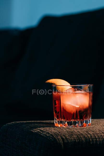 Copa de refrescante cóctel Negroni con sabor amargo y hielo adornado con cáscara de naranja y servido en el brazo del sofá en habitación oscura - foto de stock