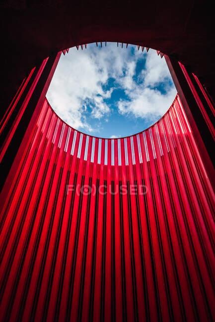 De dessous de mur géométrique rond lumineux en forme sous le ciel bleu avec des nuages dans le théâtre — Photo de stock